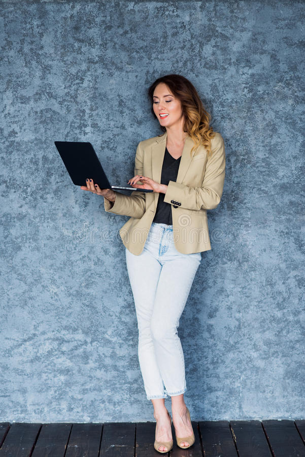 Ganzaufnahme einer glücklichen jungen Frau, die Laptop über grauem Hintergrund verwendet lizenzfreie stockfotografie