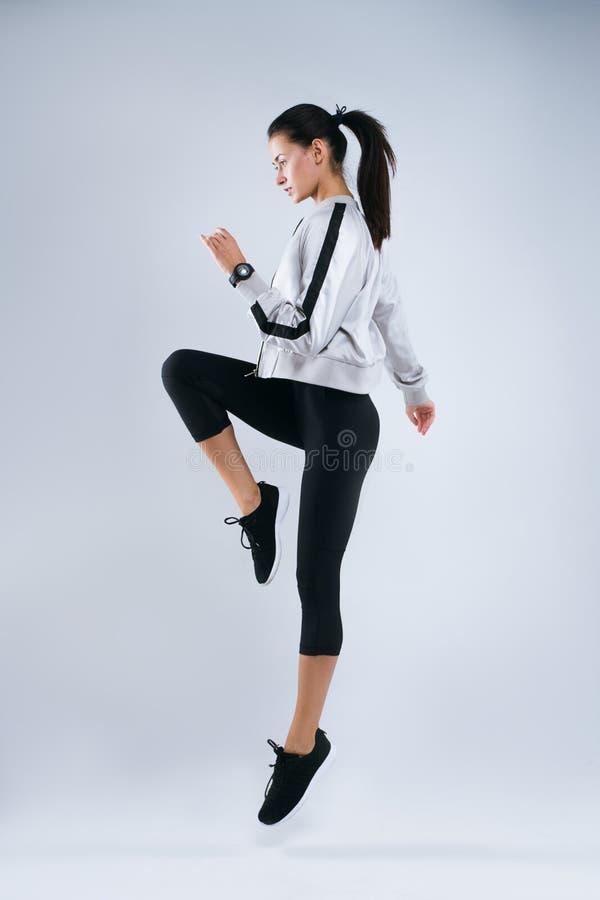 Ganzaufnahme einer jungen Eignungsfrau in der Sportkleidung, die über grauen Hintergrund aufwirft und springt lizenzfreies stockfoto