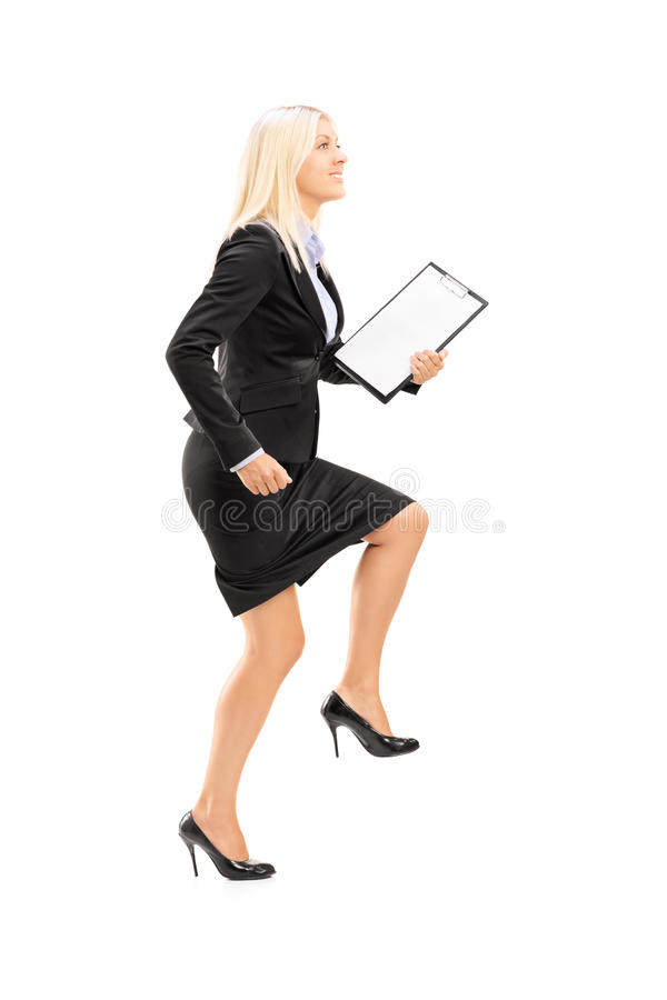 Ganzaufnahme einer jungen Geschäftsfrau, die einen gewaltigen Schritt tut stockfoto