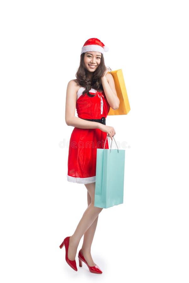 Ganzaufnahme einer lächelnden asiatischen Frau der Junge, die Einkaufstaschen vor Weihnachten hält stockfotos