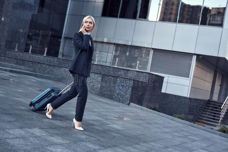 Ganzaufnahme einer lächelnden erfolgreichen Geschäftsfrau, die Koffer zieht stockfotos
