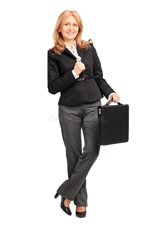 Ganzaufnahme einer reifen Geschäftsfrau, die an a sich lehnt stockfotografie