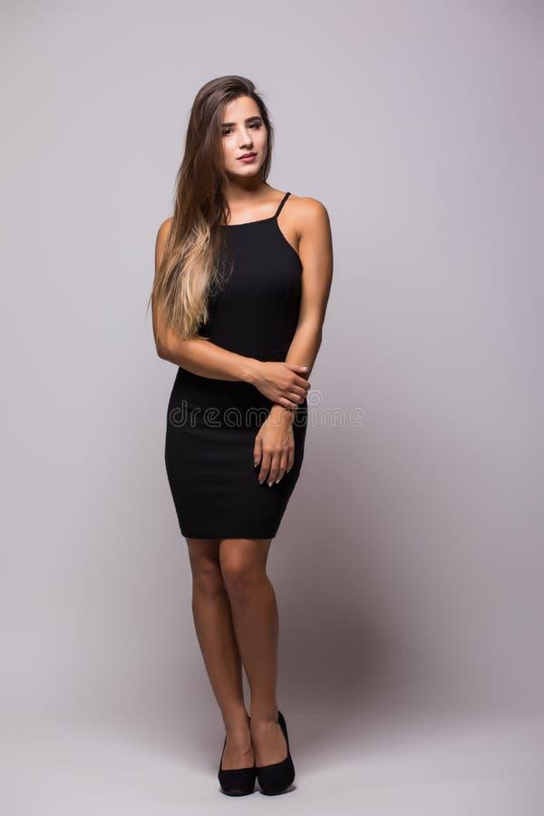 Ganzaufnahme einer sexy Frau in wenigem schwarzem Modekleid auf Grau stockfotografie