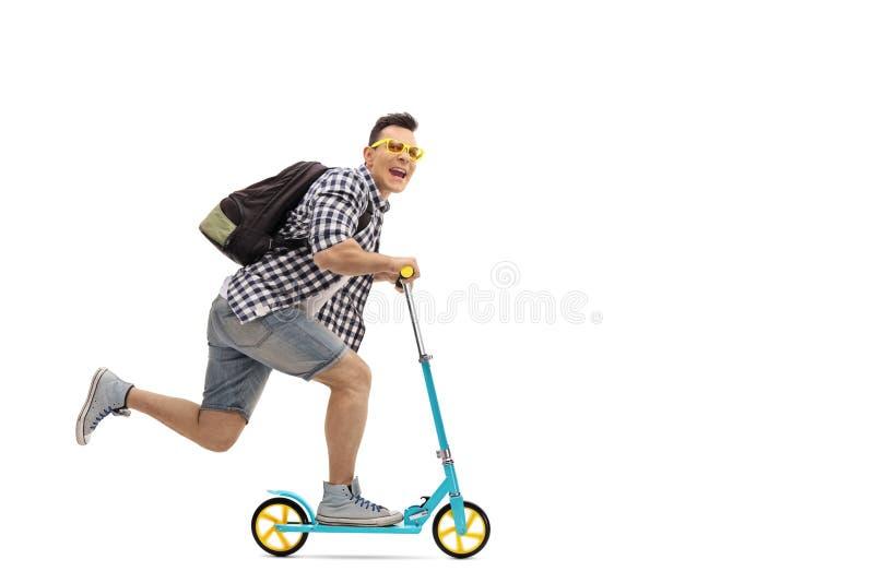 Ganzaufnahme eines überglücklichen Kerls, der einen Roller reitet lizenzfreies stockfoto
