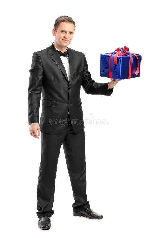 Ganzaufnahme eines eleganten Mannes, der ein Geschenk hält lizenzfreie stockbilder