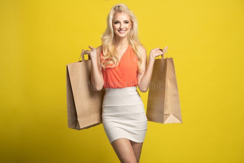 Ganzaufnahme eines glücklichen hübschen Mädchens, das Einkaufstaschen lokalisiert über gelbem Hintergrund hält stockfoto