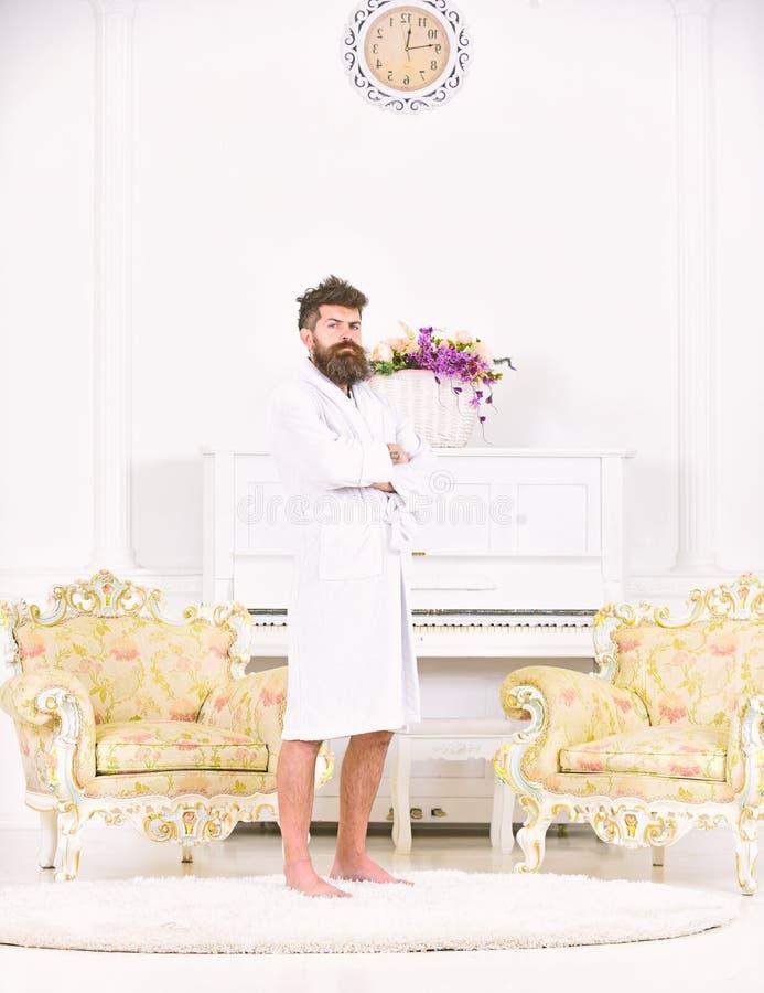 Ganzaufnahme eines jungen Mannes in einer Robe im Reinraum Grober bärtiger Kerl, der mit seinen Armen gekreuzt steht lizenzfreie stockbilder