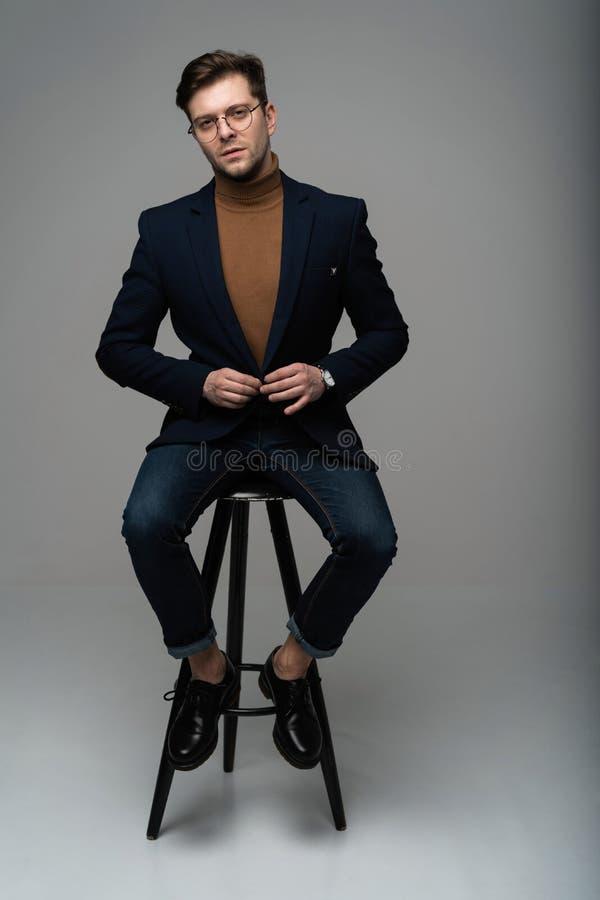 Ganzaufnahme eines jungen Modemannes, der auf einem Stuhl sitzt und die Kamera auf einem grauen Hintergrund untersucht stockbild