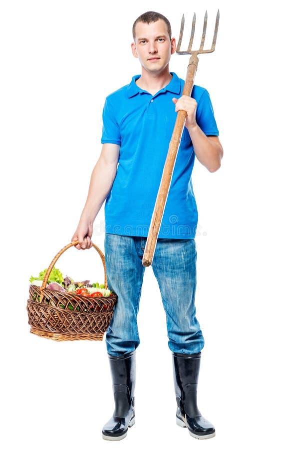 Ganzaufnahme eines Landwirts mit einer Heugabel und einem Korb lizenzfreies stockfoto