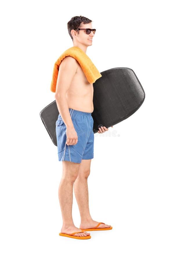 Ganzaufnahme eines männlichen Surfers, der ein Surfbrett hält stockfoto