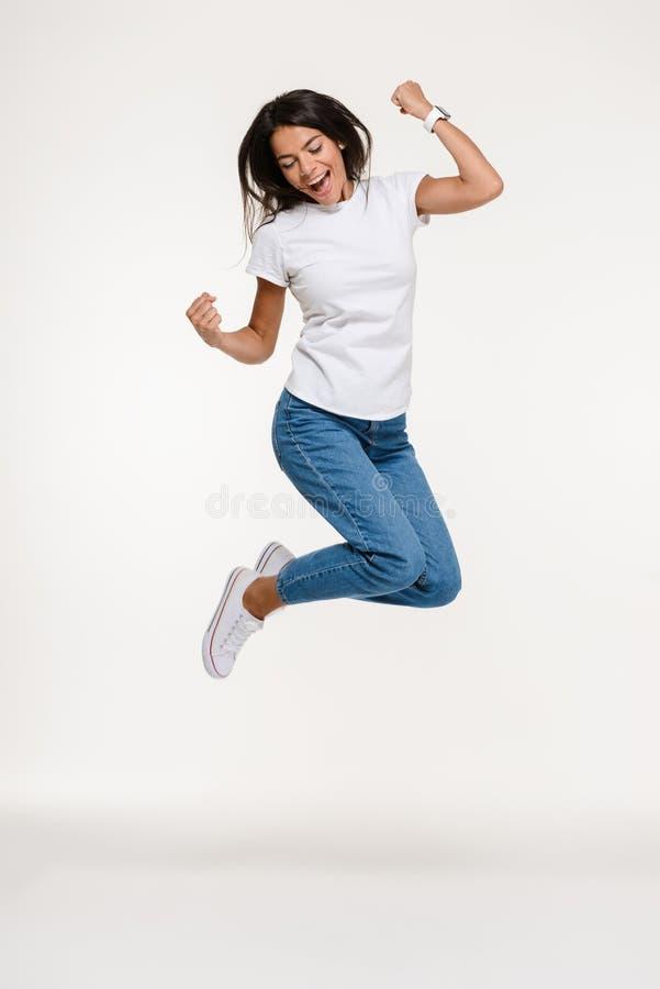 Ganzaufnahme eines recht frohen Frauenspringens lizenzfreies stockbild