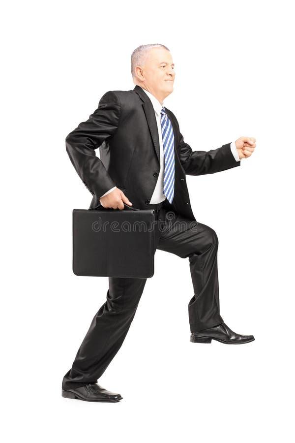 Ganzaufnahme eines reifen Geschäftsmannes, der einen gewaltigen Schritt tut lizenzfreie stockfotografie