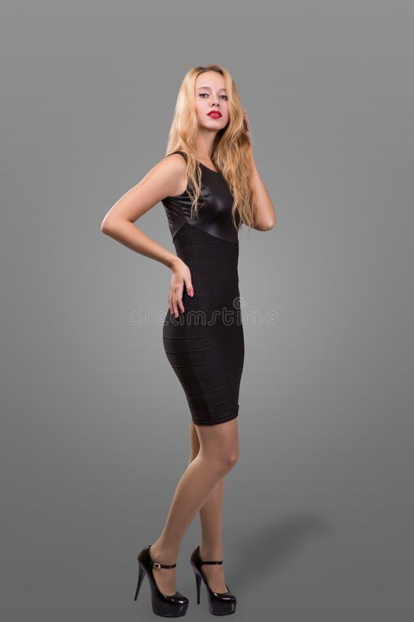 Ganzaufnahme schönen Blondine in wenigem schwarzem Mode-Kleid Grauer Hintergrund lizenzfreie stockfotografie