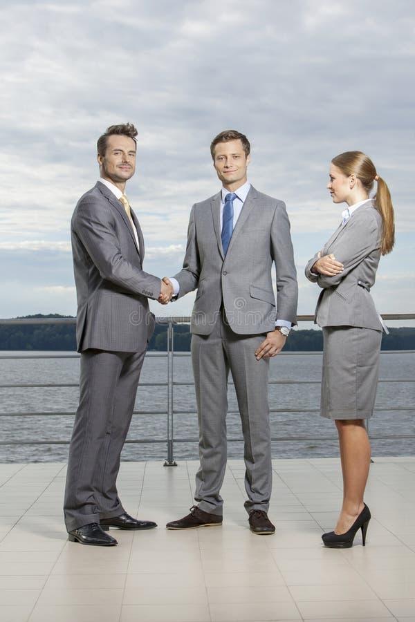 Ganzaufnahme von den jungen Geschäftsmännern, die Hände während Geschäftsfrau betrachtet sie auf Terrasse rütteln lizenzfreie stockfotografie