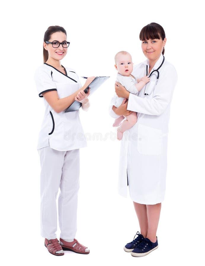 Ganzaufnahme von zwei Ärztinkinderärzten mit dem kleinen Babypatienten lokalisiert auf Weiß lizenzfreies stockfoto