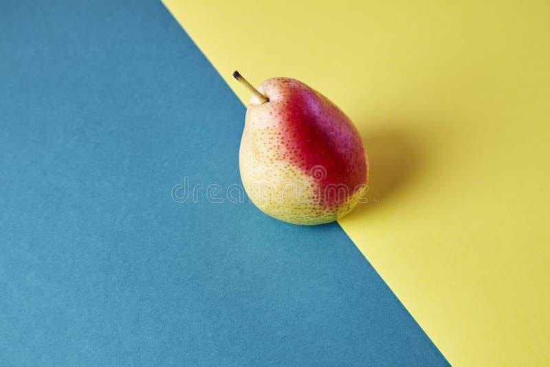 Ganze frische reife Birne, Fruchtansicht von oben genanntem auf blauem gelbem Hintergrund, modernes Artlebensmittelbild, Tapetend lizenzfreies stockfoto