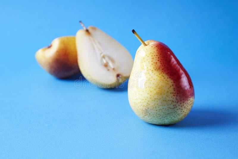 Ganze frische reife Birnen trägt auf blauem Hintergrund, modernes Artlebensmittelbild, Sommertapetendesign Früchte lizenzfreie stockfotografie