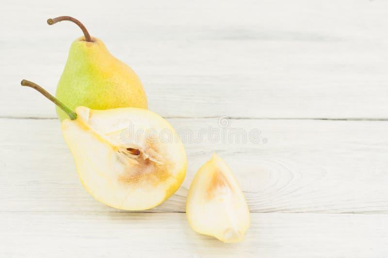 Ganze frische reife gelbe Birne und Hälfte der Birne und der Scheibe der Birne stockbild