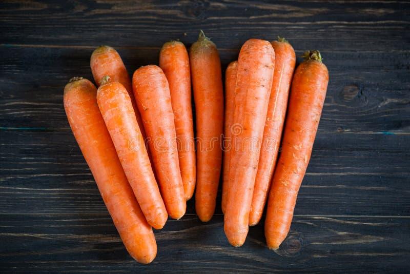 Ganze Karotten auf dunklem Holztisch stockbild
