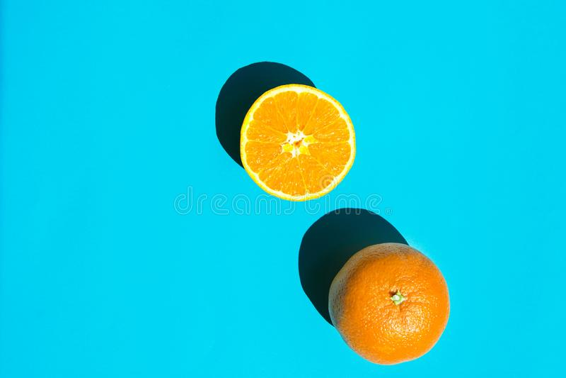 Ganze und halbierte reife saftige Orange auf blauem Hintergrund Helles raues Sonnenlicht-tiefer Schatten Vibrierende Neonfarben S stockbild