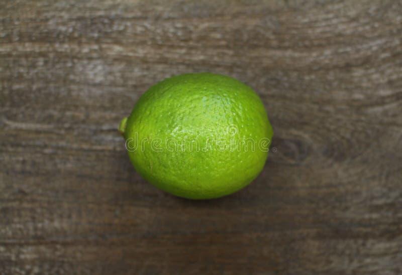 Ganzer grüner Kalk auf dunkler Holzoberfläche lizenzfreies stockbild