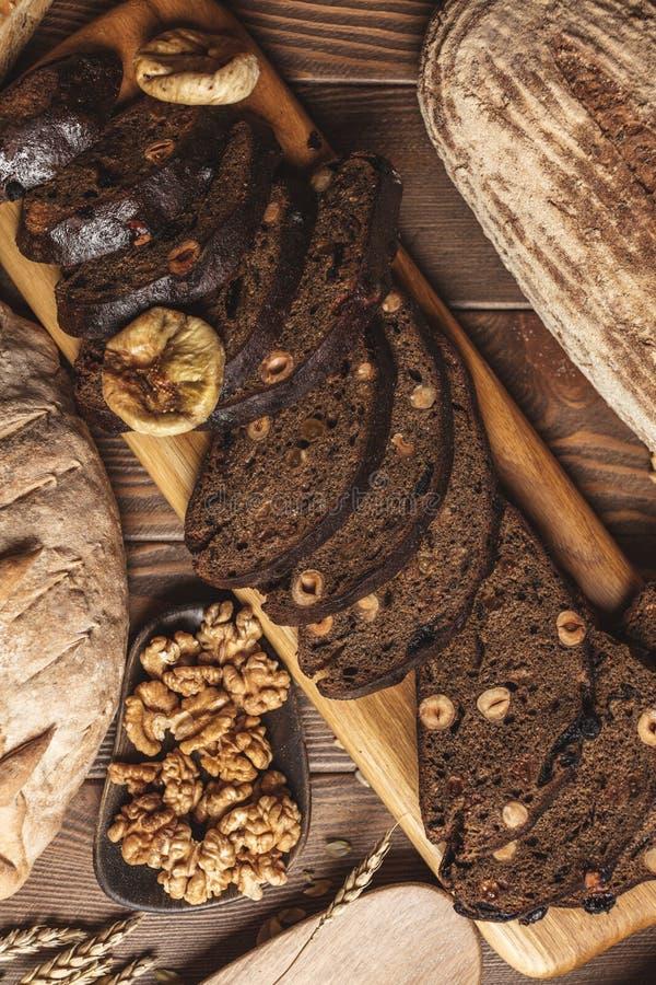 Ganzes Korn multigrain Brot, ganz und geschnitten, enth?lt die Samen, die auf Schwarzem lokalisiert werden lizenzfreies stockbild