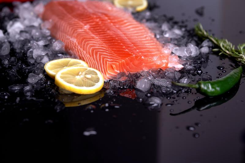 Ganzes rohes Lachsfilet mit Scheiben der Zitrone und des grünen Paprikas auf zerquetschtem Eis auf einem schwarzen Hintergrund Di stockfotos