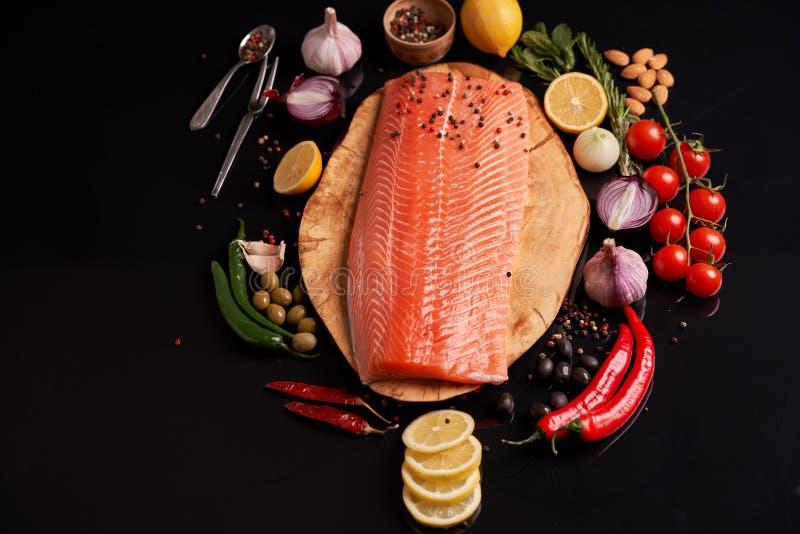 Ganzes rotes Fischfilet auf einer h?lzernen Platte mit den Kirschtomaten-, Roten und Gr?nenpaprikapfeffer-, Schwarzen und Gr?neno stockfoto
