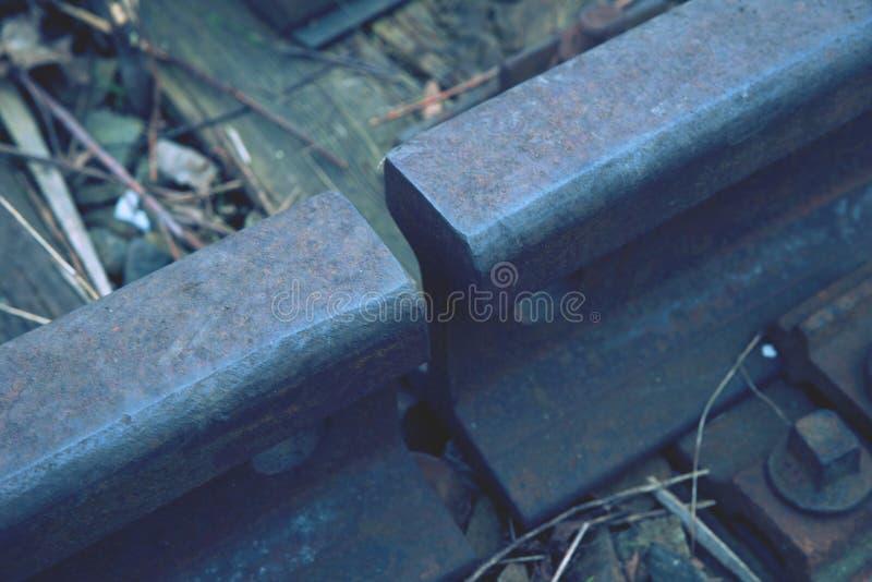 Gap met noot en schroef op het oude roestige spoor Het roestige detail van de treinspoorweg, geoli?de dwarsbalken stock fotografie