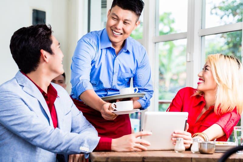 Garçom asiático amigável que serve um café dos pares fotografia de stock royalty free