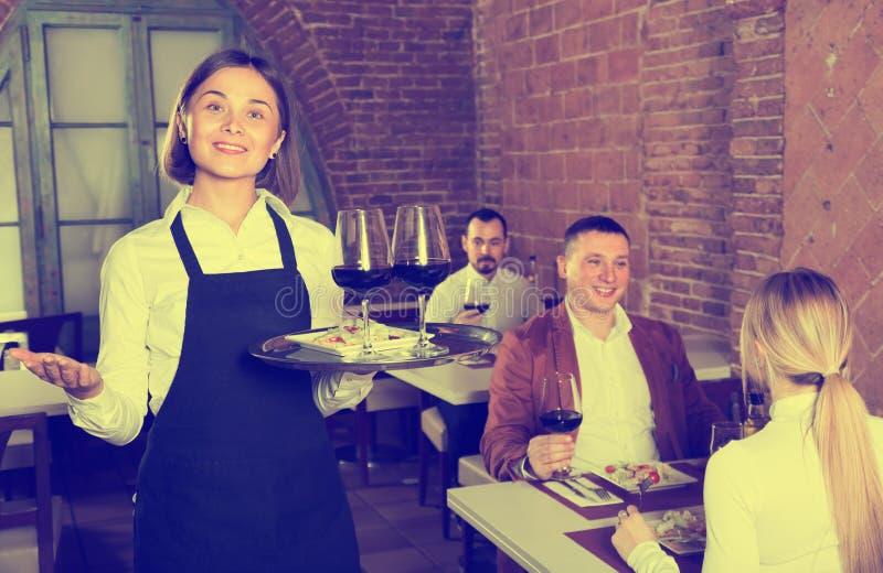 Garçom atento da mulher que demonstra o restaurante aos visitantes foto de stock royalty free