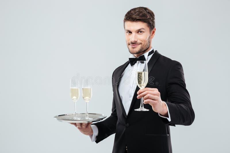 Garçom atrativo no smoking que guarda a bandeja e o vidro do champanhe fotos de stock