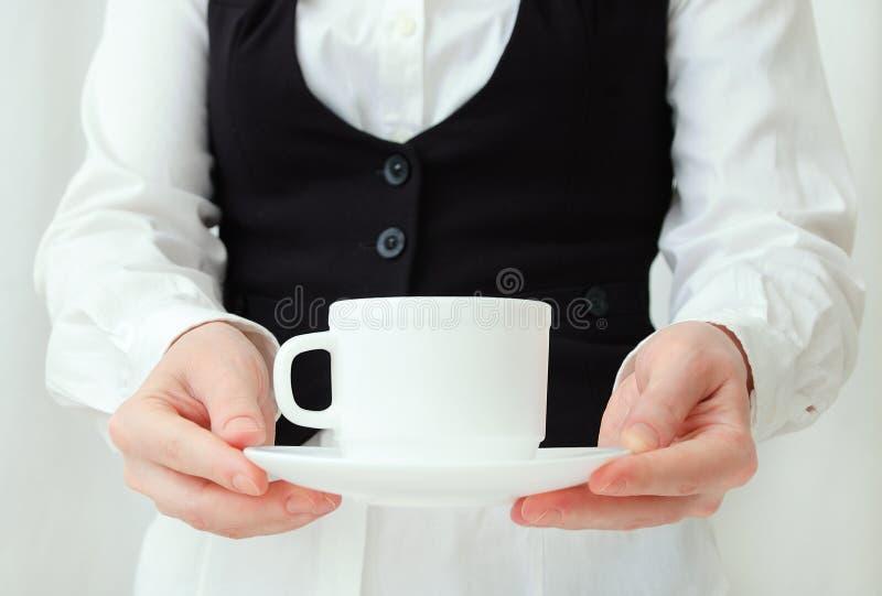 Garçom caucasiano da menina na camisa branca e na veste preta com pares do chá nas mãos imagens de stock royalty free