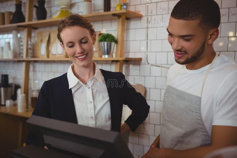 Garçom com o proprietário que olha na caixa registadora no café fotos de stock royalty free