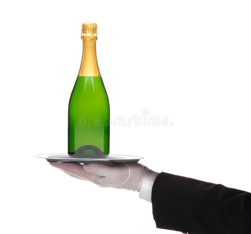 Garçom com uma bandeja e uma garrafa de prata do champanhe em sua mão estendido imagem de stock royalty free