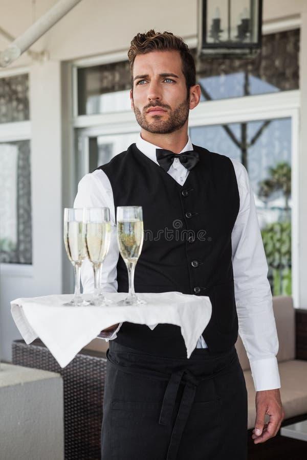 Garçom considerável que guarda a bandeja de champanhe fotos de stock