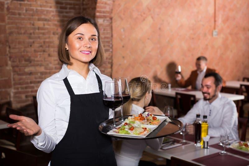 Garçom da jovem mulher que demonstra o restaurante aos visitantes fotografia de stock