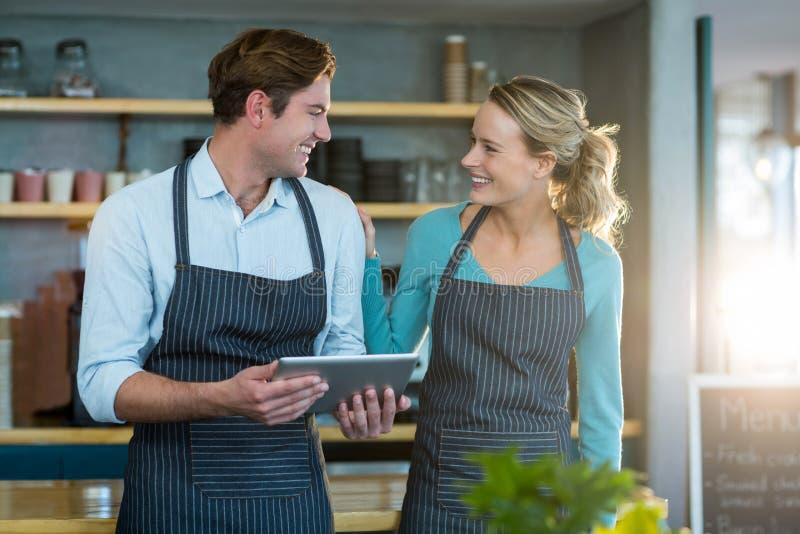 Garçom e empregada de mesa de sorriso que interagem ao usar a tabuleta digital fotografia de stock royalty free