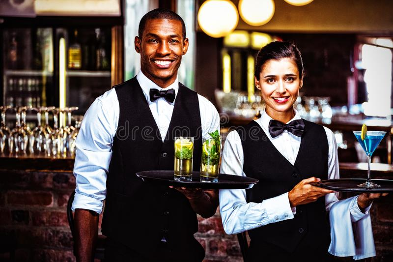 Garçom e empregada de mesa que guardam uma bandeja do serviço com vidro do cocktail foto de stock