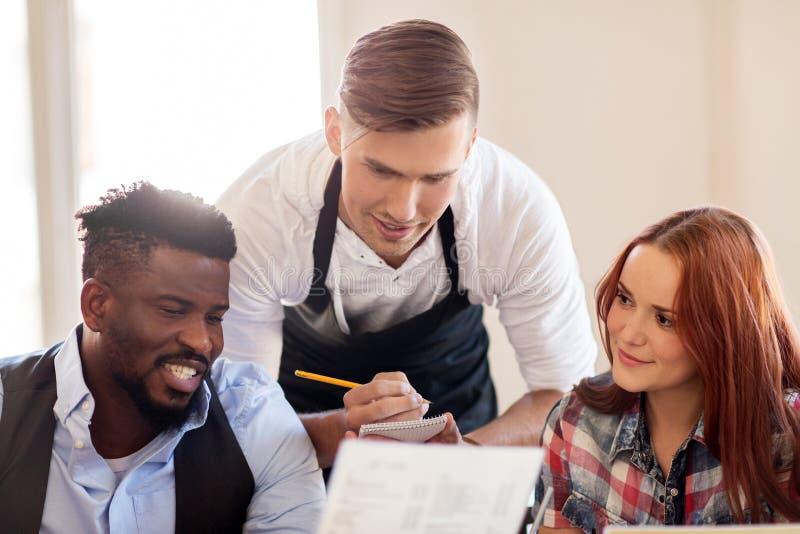Garçom e pares com menu no restaurante fotos de stock royalty free