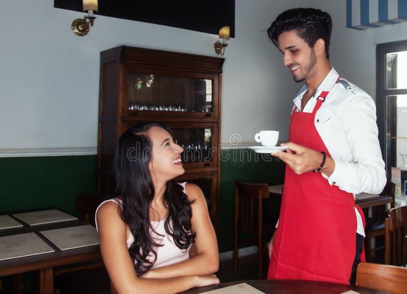 Garçom latino-americano que serve a xícara de café a um convidado foto de stock