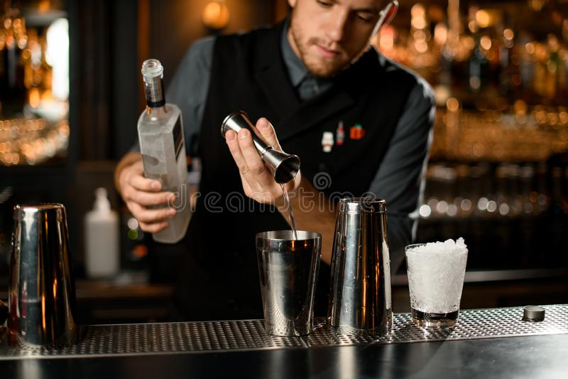 Garçom masculino lançando uma vodka do jigger para um agitador de aço segurando uma garrafa fotografia de stock