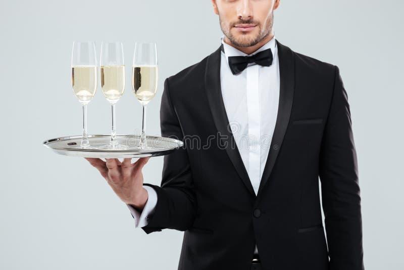 Garçom no smoking que guarda a bandeja com vidros do champanhe fotografia de stock