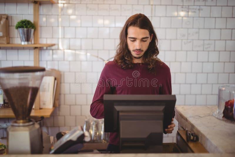 Garçom novo com cabelo longo usando a caixa registadora na cafetaria fotos de stock