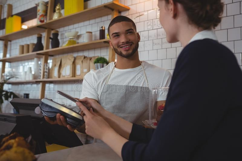 Garçom novo que mostra o leitor de cartão do crédito ao proprietário no café fotografia de stock royalty free