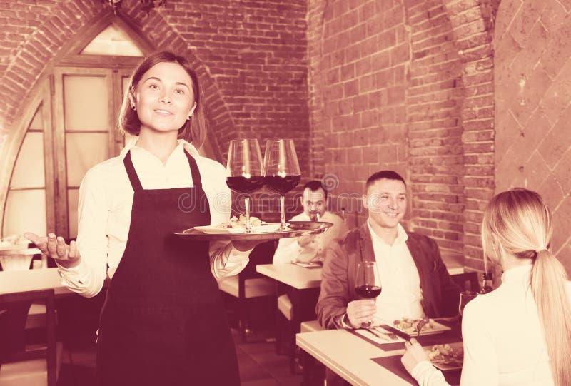 Garçom positivo da mulher que demonstra o restaurante aos visitantes fotos de stock