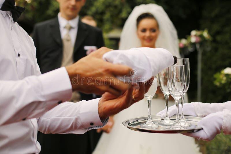 Garçom Pouring Champagne Into Glasses foto de stock