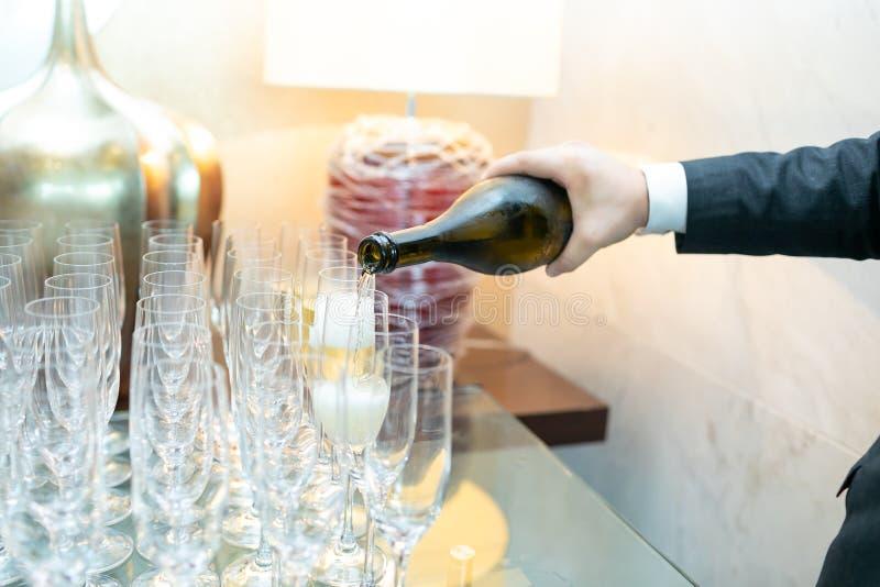 Garçom que derrama o champanhe frio em vidros no fundo das lâmpadas imagens de stock royalty free