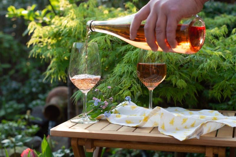 Garçom que derrama o vinho cor-de-rosa frio nos vidros no terraço exterior em g imagem de stock royalty free