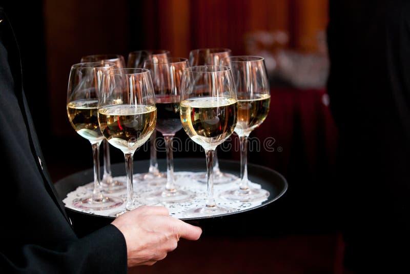 Garçom que guarda uma bandeja completamente de bebidas durante um casamento abastecido ou o outro evento especial fotos de stock royalty free